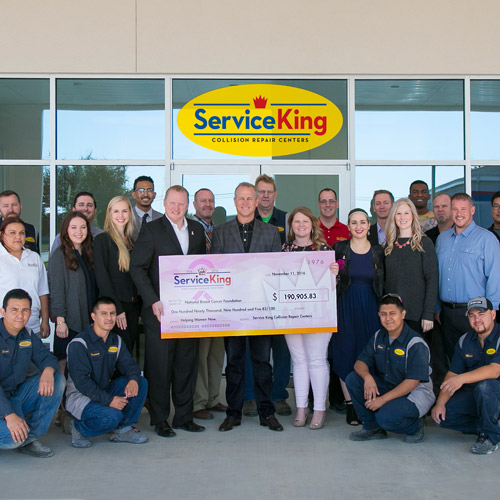 Employees at Service King display a large National Breast Cancer Foundation corporate sponsorship check for $190,905.83.
